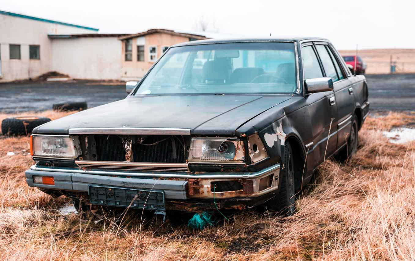 old car sitting in junkyard